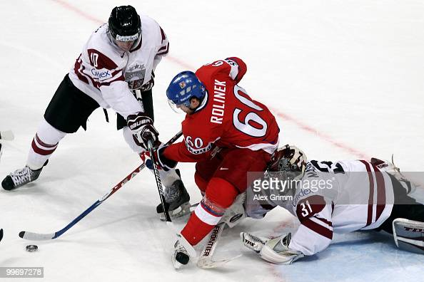Tomas Rolinek of Czech Republic is challenged by Lauris Darzins and goalkeeper Edgars Masalskis of Latvia during the IIHF World Championship group F...