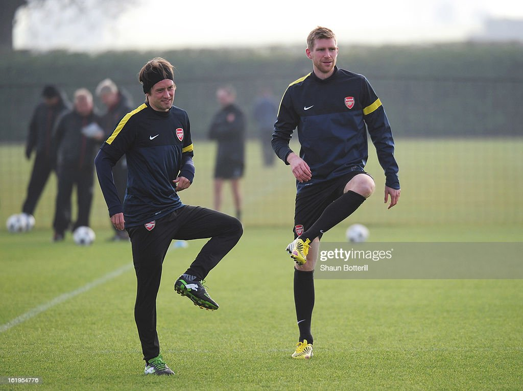 Tomas Rosicky and Per Mertesacker (R) of Arsenal warm up during a training session ahead of their UEFA Champions League round of 16 first leg match against FC Bayern Muenchen at London Colney on February 18, 2013 in St Albans, England.