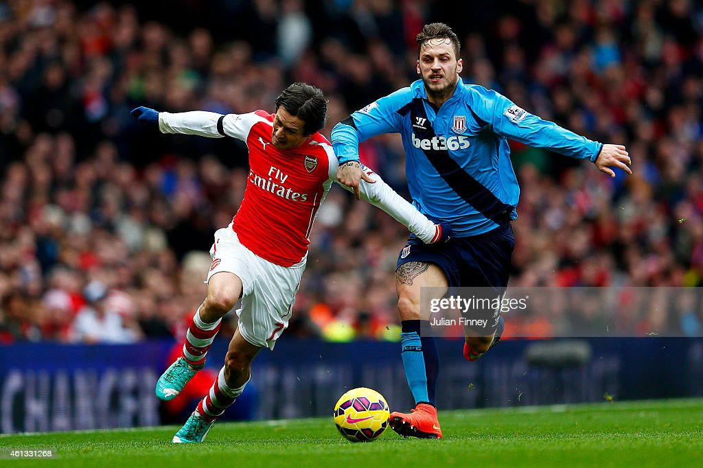 Tomas Rosicky of Arsenal battles for the ball with Marko Arnautovic of Stoke City during the Barclays Premier League match between Arsenal and Stoke City at Emirates Stadium on January 11, 2015 in London, England.