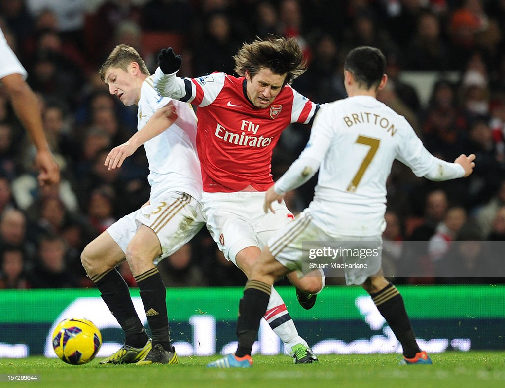 <a gi-track='captionPersonalityLinkClicked' href=/galleries/search?phrase=Tomas+Rosicky&family=editorial&specificpeople=213988 ng-click='$event.stopPropagation()'>Tomas Rosicky</a> of Arsenal challenged by (L) Ben Davies and (R) Leon Britton of Swansea during the Barclays Premier League match between Arsenal and Swansea City, at Emirates Stadium on December 01, 2012 in London, England.