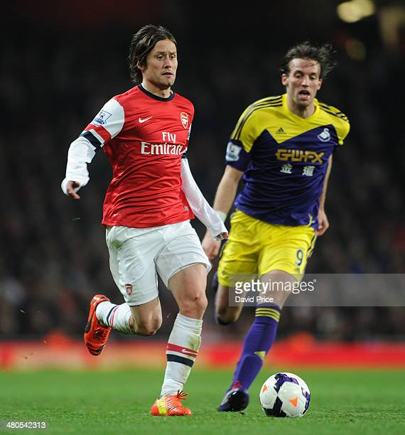 Tomas Rosicky of Arsenal takes on Miguel Michu of Swansea during the match between Arsenal and Swansea City in the Barclays Premier League at...