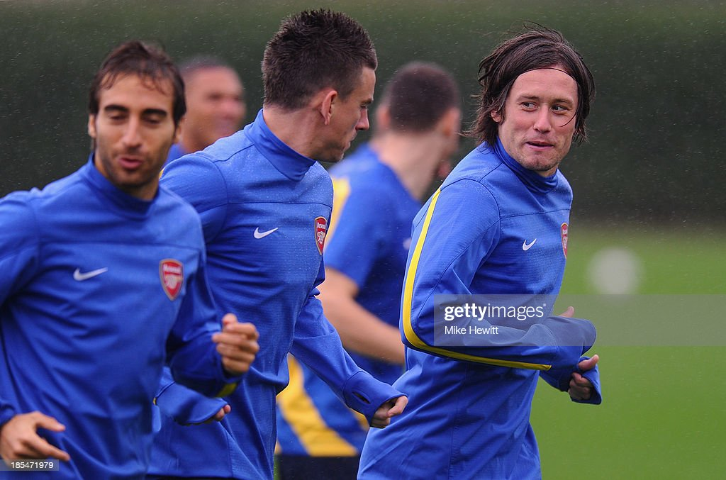 Tomas Rosicky of Arsenal (R) warms up warm up during a wet Arsenal training session ahead of the UEFA Champions League Group F match against Borussia Dortmund at London Colney on October 21, 2013 in St Albans, England.