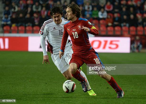 Tomas Rosicky of Czech Republic and Igors Tarasovs of Latvia vie for the ball during the Group A Euro 2016 qualifying football match between Czech...