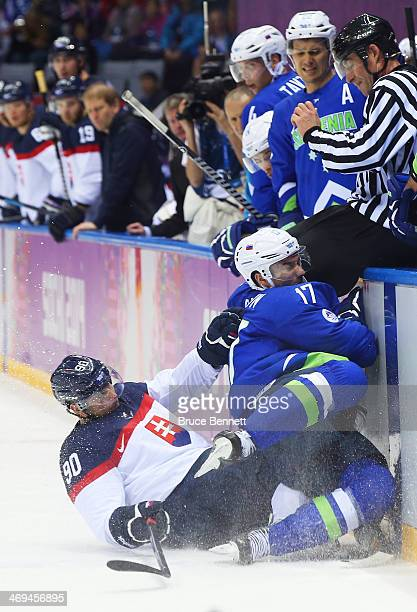 Tomas Tatar of Slovakia collides with Ziga Pavlin of Slovenia in the second period during the Men's Ice Hockey Preliminary Round Group A game on day...