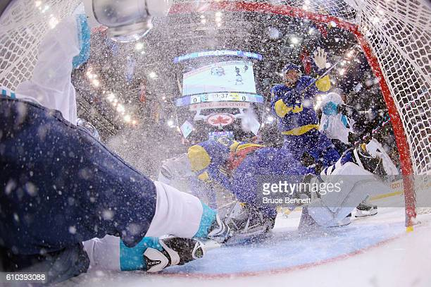 Tomas Tatar of Team Europe slides into the net past Henrik Lundqvist of Team Sweden during the first period at the semifinal game during the World...