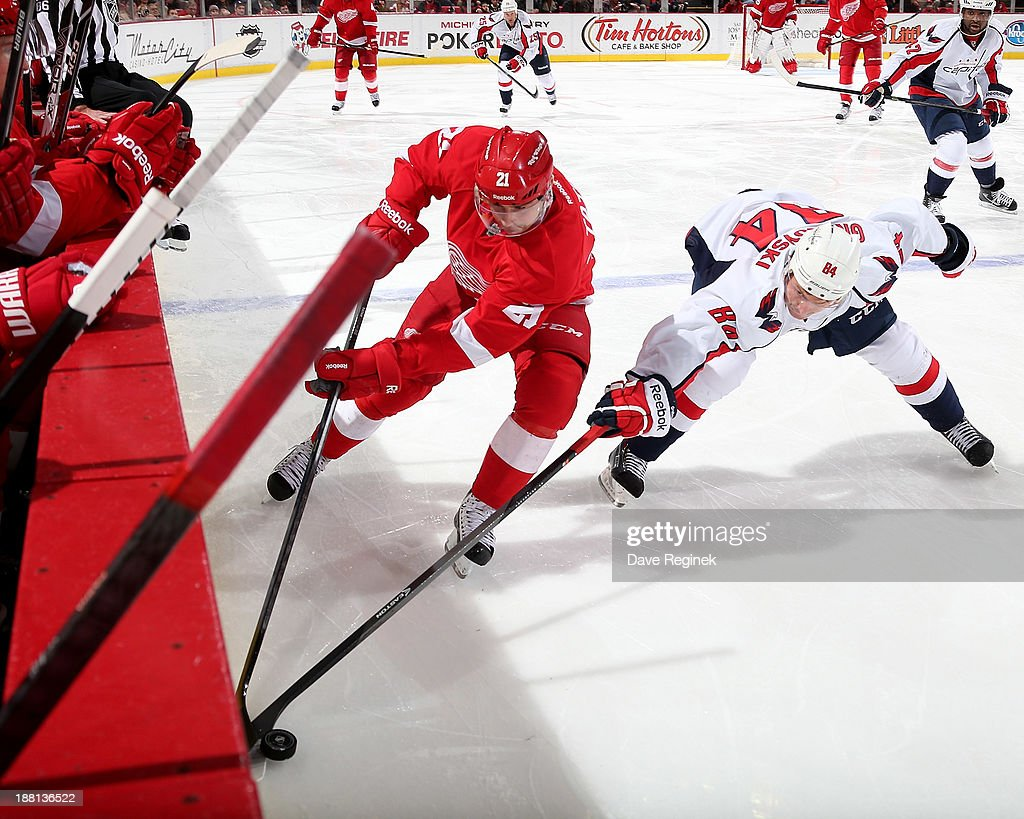 <a gi-track='captionPersonalityLinkClicked' href=/galleries/search?phrase=Tomas+Tatar&family=editorial&specificpeople=5652303 ng-click='$event.stopPropagation()'>Tomas Tatar</a> #21 of the Detroit Red Wings and <a gi-track='captionPersonalityLinkClicked' href=/galleries/search?phrase=Mikhail+Grabovski&family=editorial&specificpeople=2560547 ng-click='$event.stopPropagation()'>Mikhail Grabovski</a> #84 of the Washington Capitals battle for the puck along the boards during an NHL game at Joe Louis Arena on November 15, 2013 in Detroit, Michigan.