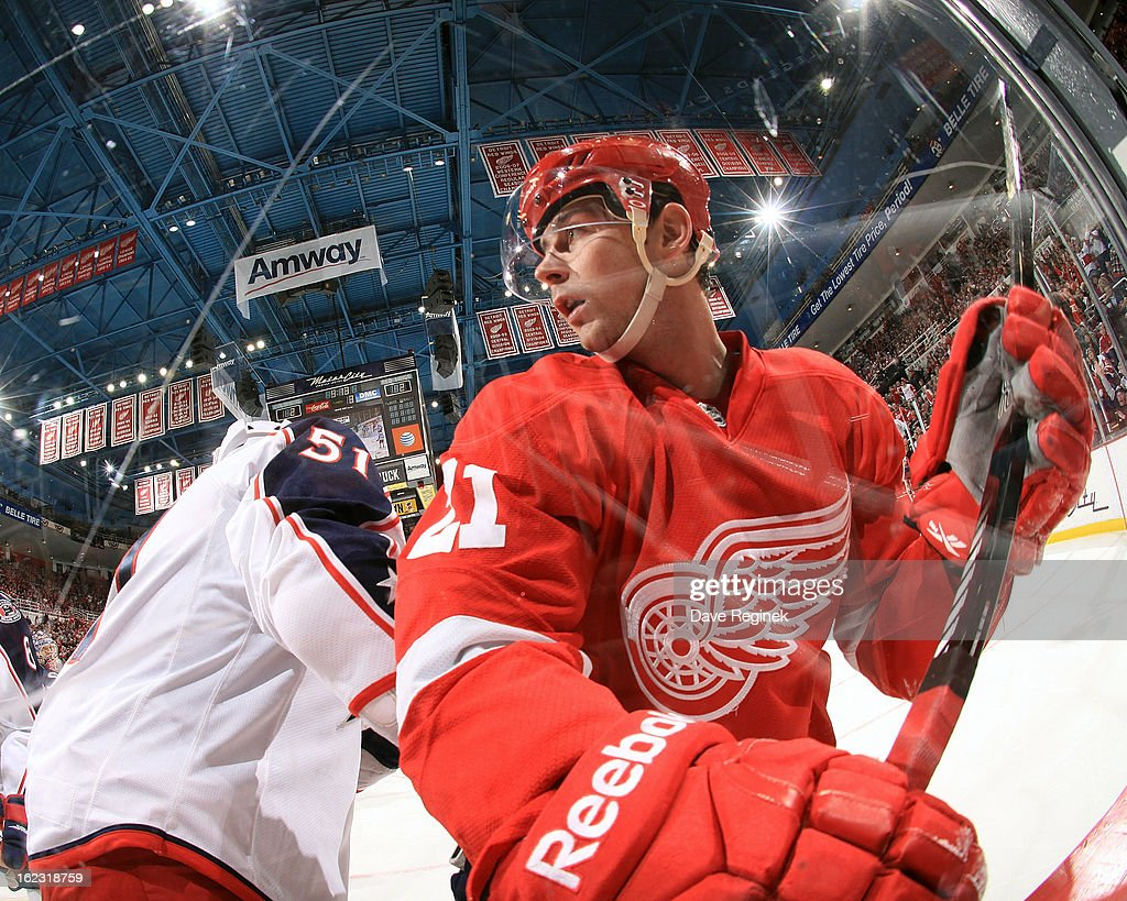 Tomas Tatar #21 of the Detroit Red Wings battles along the boards with Fedor Tyutin #51 of the Columbus Blue Jackets during a NHL game at Joe Louis Arena on February 21, 2013 in Detroit, Michigan. Columbus won 3-2