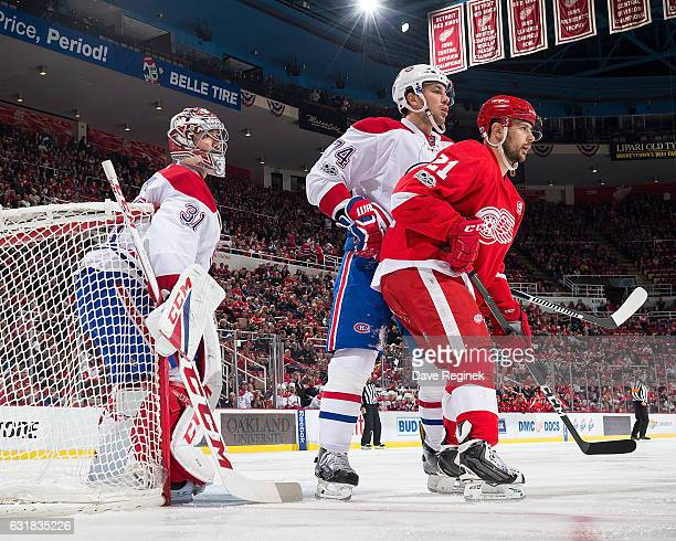 Tomas Tatar of the Detroit Red Wings battles for position with Alexei Emelin of the Montreal Canadiens in front of teammate Carey Price of the...