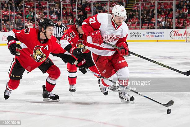 Tomas Tatar of the Detroit Red Wings battles for the puck with Kyle Turris and Alex Chiasson of the Ottawa Senators during an NHL game at Joe Louis...
