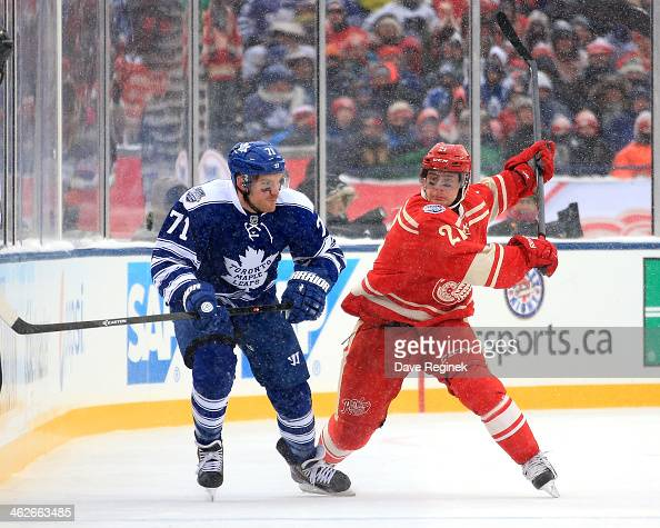 Tomas Tatar of the Detroit Red Wings body checks David Clarkson of the Toronto Maple Leafs during the Bridgestone NHL Winter Classic on January 1...