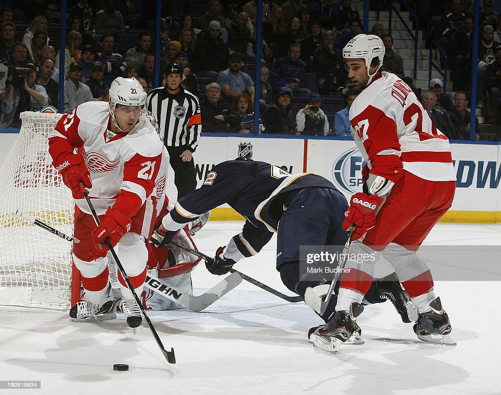 Tomas Tatar #21 of the Detroit Red Wings controls the puck as David Backes #42 of the St. Louis Blues is pushed down by Kyle Quincey #27 of the Detroit Red Wings in an NHL game on February 7, 2013 at Scottrade Center in St. Louis, Missouri.
