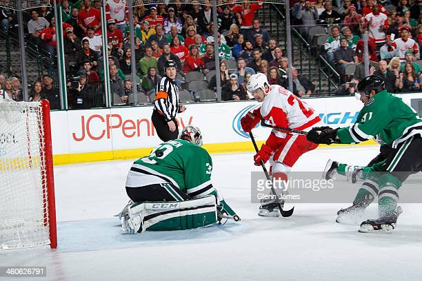 Tomas Tatar of the Detroit Red Wings flips a puck into the net against Kari Lehtonen of the Dallas Stars at the American Airlines Center on January 4...