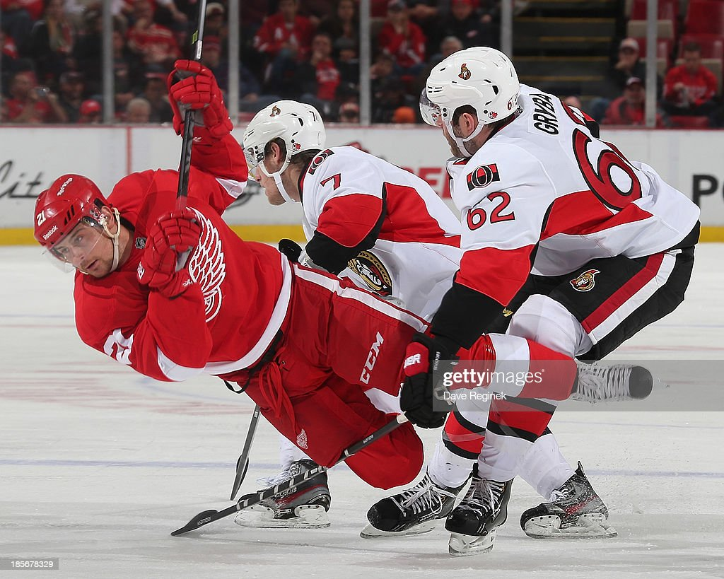 <a gi-track='captionPersonalityLinkClicked' href=/galleries/search?phrase=Tomas+Tatar&family=editorial&specificpeople=5652303 ng-click='$event.stopPropagation()'>Tomas Tatar</a> #21 of the Detroit Red Wings is tripped up by Eric Gryba #62 of the Ottawa Senators during an NHL game at Joe Louis Arena on October 23, 2013 in Detroit, Michigan. The Senators win 6-1