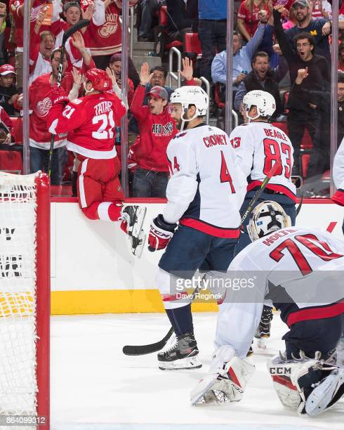 Tomas Tatar of the Detroit Red Wings jumps against the glass in celebration after scoring his second goal of the third period as Taylor Chorney Jay...