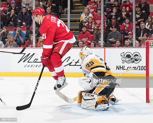Tomas Tatar of the Detroit Red Wings jumps out of the way of a shot in front of goaltender MarcAndre Fleury of the Pittsburgh Penguins during an NHL...