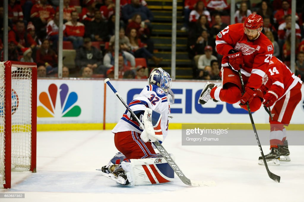 Tomas Tatar #21 of the Detroit Red Wings jumps out of the way of a shot in front of Antti Raanta #32 of the New York Rangers during the third period at Joe Louis Arena on March 12, 2017 in Detroit, Michigan. New York won the game 4-1.