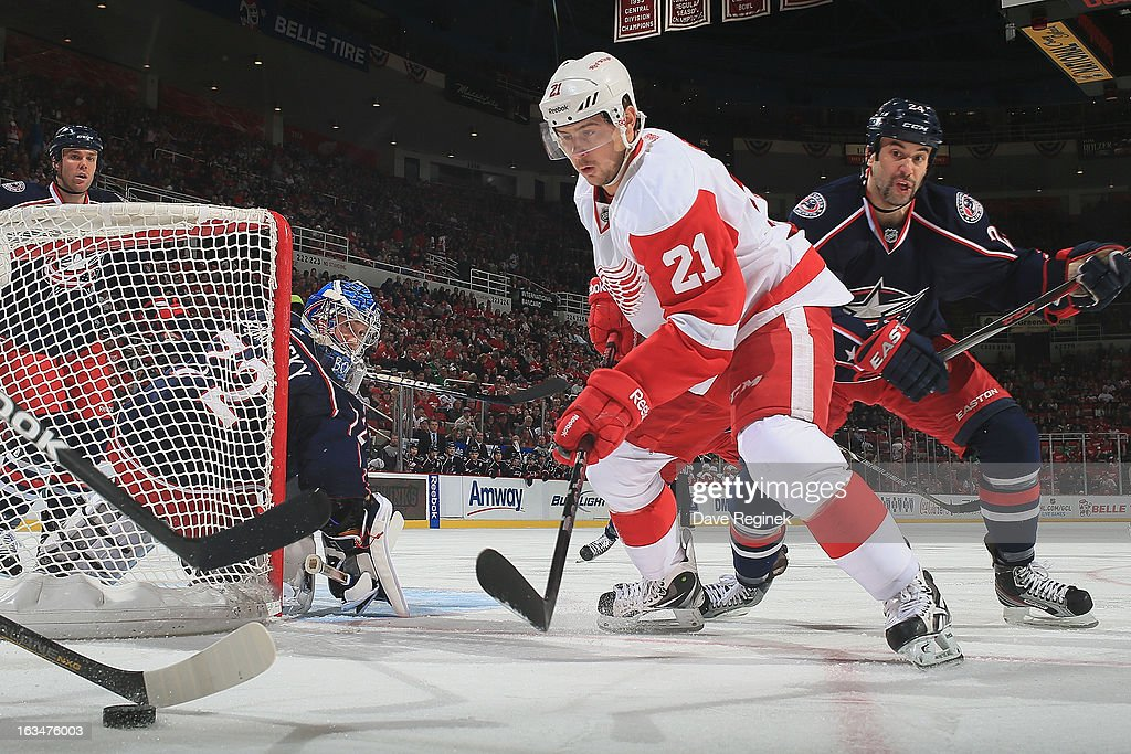 Tomas Tatar #21 of the Detroit Red Wings looks for the puck in front of <a gi-track='captionPersonalityLinkClicked' href=/galleries/search?phrase=Derek+MacKenzie&family=editorial&specificpeople=685877 ng-click='$event.stopPropagation()'>Derek MacKenzie</a> #24 of the Columbus Blue Jackets during an NHL game at Joe Louis Arena on March 10, 2013 in Detroit, Michigan.