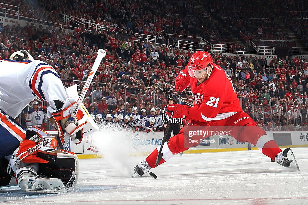 Tomas Tatar #21 of the Detroit Red Wings makes a move with the puck and beats Viktor Fasth #35 of the Edmonton Oilers in a shootout to clinch the win during an NHL game on March 14, 2014 at Joe Louis Arena in Detroit, Michigan. Detroit defeated Edmonton 2-1 in a shootout