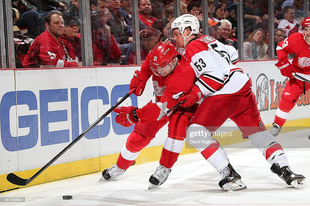 <a gi-track='captionPersonalityLinkClicked' href=/galleries/search?phrase=Tomas+Tatar&family=editorial&specificpeople=5652303 ng-click='$event.stopPropagation()'>Tomas Tatar</a> #21 of the Detroit Red Wings protects the puck as <a gi-track='captionPersonalityLinkClicked' href=/galleries/search?phrase=Jeff+Skinner&family=editorial&specificpeople=3147596 ng-click='$event.stopPropagation()'>Jeff Skinner</a> #53 of the Carolina Hurricanes tries to knock him off it during an NHL game at Joe Louis Arena on November 21, 2013 in Detroit, Michigan. Detroit defeated Carolina 4-3