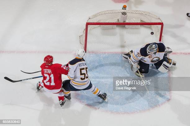 Tomas Tatar of the Detroit Red Wings scores a second period goal on Robin Lehner of the Buffalo Sabres while being defended by Rasmus Ristolainen of...