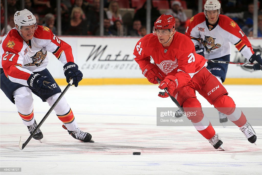 <a gi-track='captionPersonalityLinkClicked' href=/galleries/search?phrase=Tomas+Tatar&family=editorial&specificpeople=5652303 ng-click='$event.stopPropagation()'>Tomas Tatar</a> #21 of the Detroit Red Wings skates with the puck as <a gi-track='captionPersonalityLinkClicked' href=/galleries/search?phrase=Nick+Bjugstad&family=editorial&specificpeople=7029343 ng-click='$event.stopPropagation()'>Nick Bjugstad</a> #27 of the Florida Panthers reaches in to knock it away during an NHL game at Joe Louis Arena on December 7, 2013 in Detroit, Michigan. Florida defeated Detroit 2-1