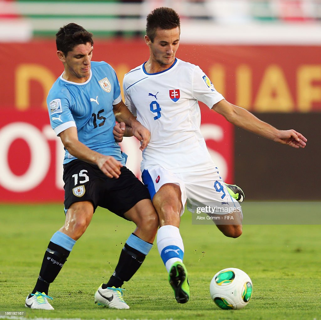 Tomas Vestenicky (R) of Slovakia is challenged by Gaston Faber of Uruguay during the FIFA U-17 World Cup UAE 2013 Round of 16 match between Uruguay and Slovakia at Ras Al Khaimah Stadium on October 29, 2013 in Ras al Khaimah, United Arab Emirates.