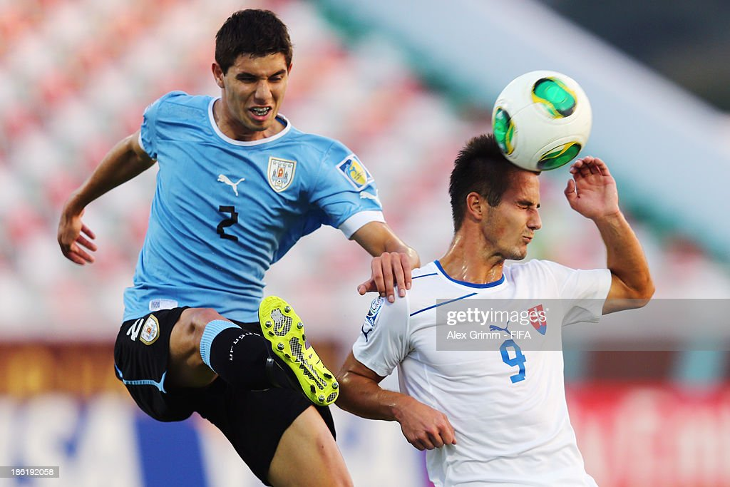 Tomas Vestenicky (R) of Slovakia is challenged by Joel Bregonis of Uruguay during the FIFA U-17 World Cup UAE 2013 Round of 16 match between Uruguay and Slovakia at Ras Al Khaimah Stadium on October 29, 2013 in Ras al Khaimah, United Arab Emirates.