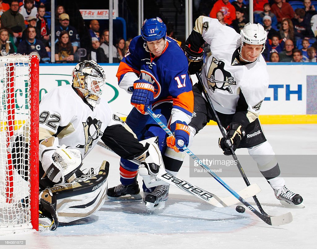 Tomas Vokoun #92 and Mark Eaton #4 of the Pittsburgh Penguins defend the net against Matt Martin #17 of the New York Islanders in an NHL hockey game at Nassau Veterans Memorial Coliseum on March 22, 2013 in Uniondale, New York.