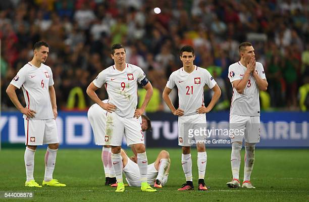 Tomasz Jodlowiec Robert Lewandowski Cedric Soares and Pepe of Portugal show their dejection after their defeat through the panelty shootout in the...