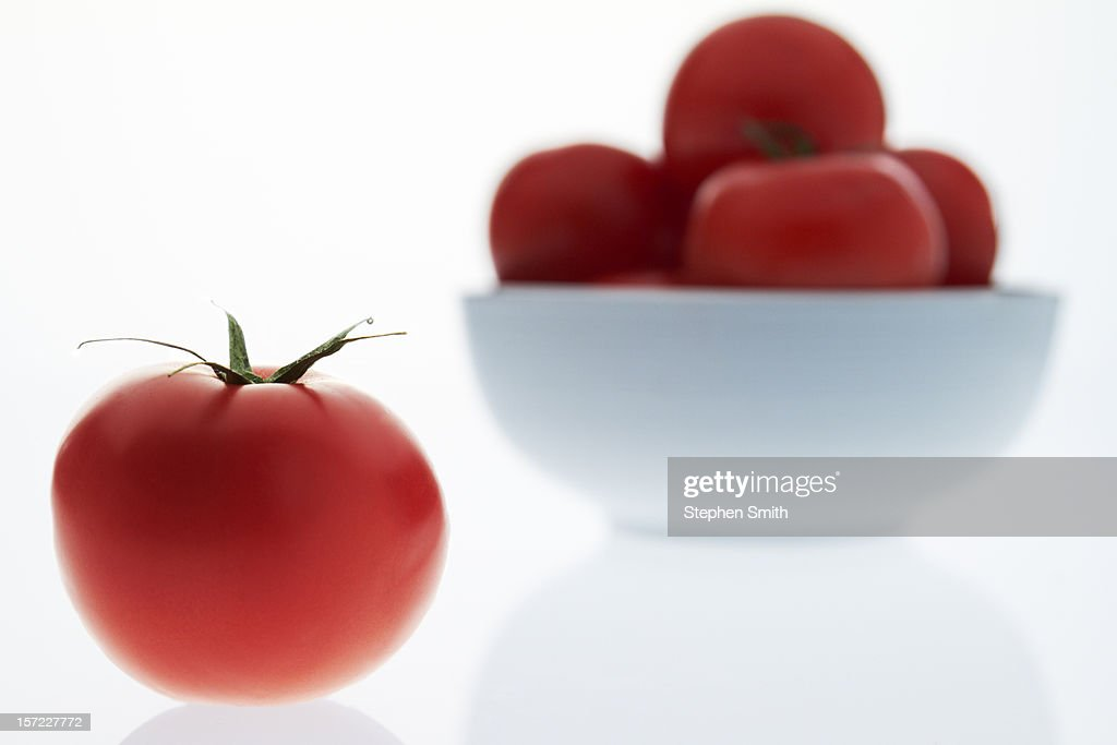 A tomato and a bowl of tomatoes : Stock Photo