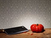 Tomato and cleaver on chopping board