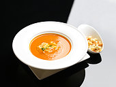 Tomato cream soup garnished with crisp bread crackers on a white and black background