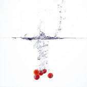 tomato fallng into water on white background