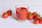 Tomato juice and fresh tomatoes on a white wooden table