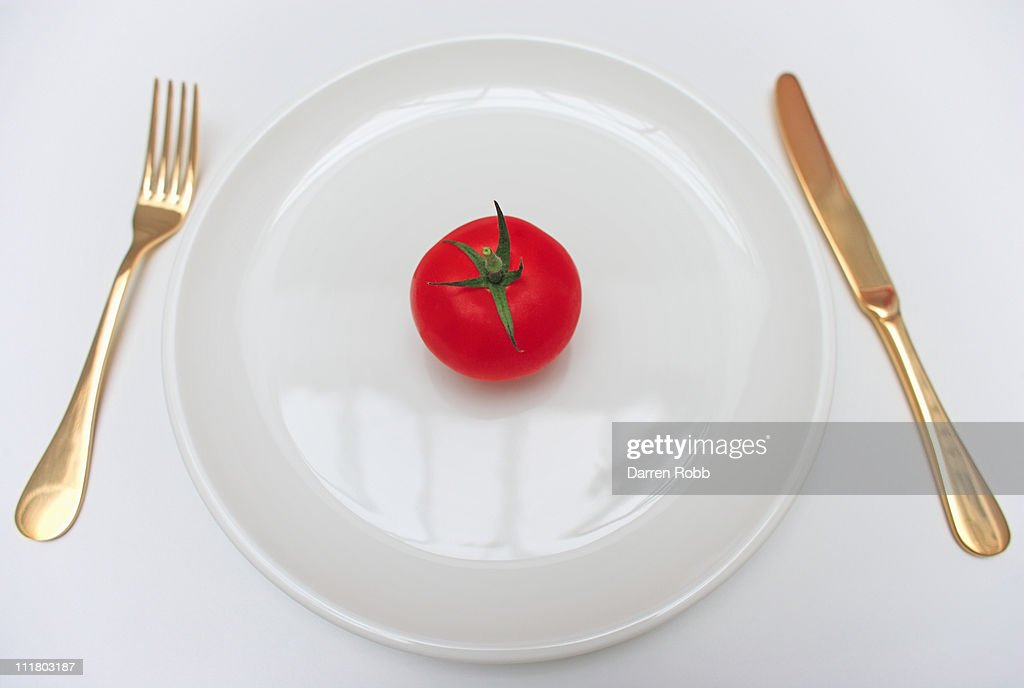 Tomato on a dinner plate with knife and fork : Stock Photo