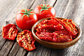 Fresh and dried tomato on a wooden background