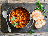 Tomato sauce braised chickpeas in a pot, and grilled bread. Delicious vegetarian lunch on a rustic wooden background, top view