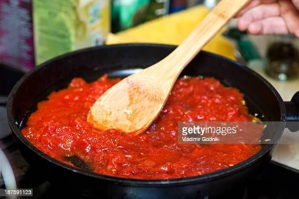 Tomato sauce in frying pan with wooden spatula