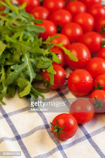 Tomatoes and arugula on towel : Stock Photo