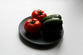 Two tomatoes and green poblano pepper isolated on gray concrete plate