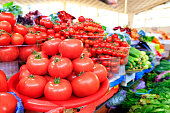 Different varieties of ripe red tomatoes in the background in a blur of cucumbers, spinach and other vegetables sold in trays on the market
