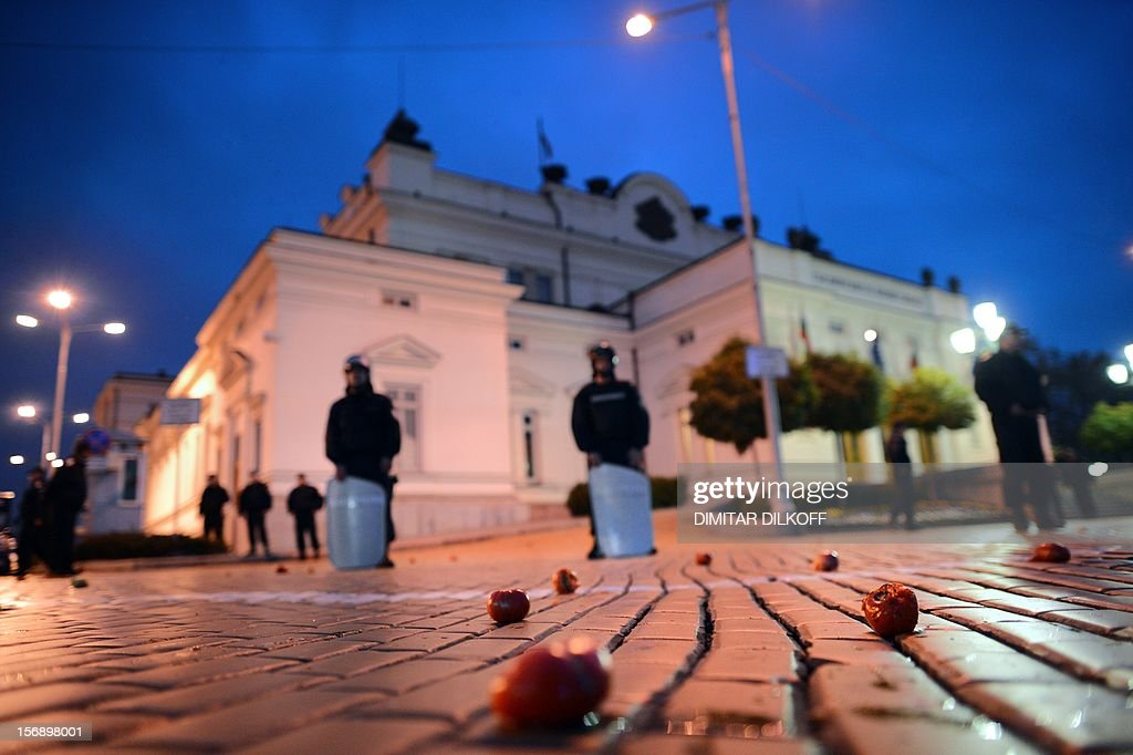 Tomatoes lay on the ground as policemen stand guard in front of the Parliament building in Sofia on November 24, 2012. Government-weary Bulgarians literally saw red on Saturday, gathering to throw tomatoes at the parliament building in the Bulgarian capital. Some 200 protesters joined in the demo, shouting 'Mafia!' and 'Political garbage!' to protest the brief arrest on Tuesday of famous anti-communist dissident and poet Nikolay Kolev.