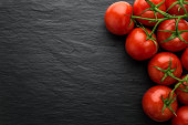 Close up of freshly picked tomatoes on dark stone background with copy space