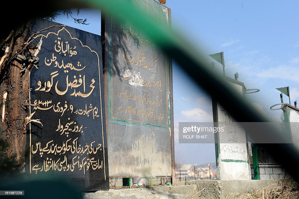 A tomb stone for Kashmiri separatist, Afzal Guru (L), is seen at the Martyres Graveyard in Srinagar on February 12, 2013, and reads, 'His mortal remains are lying in trust with the government of India, the Kashmiri nation awaits its return.' Guru, a Kashmiri separatist was executed on February 9, 2013 over his role in a deadly attack on parliament in New Delhi in 2001, an episode that brought nuclear-armed India and Pakistan to the brink of war. A former fruit seller, he was hanged at Tihar Jail on the outskirts of the capital after his final appeal for mercy was rejected by President Pranab Mukherjee. AFP PHOTO/ Rouf BHAT