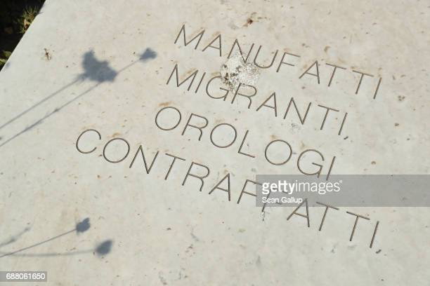 A tomb with an inscription of part of a poem in Italian lies among tombs that contain the bodies of migrants who died while trying to reach Italy in...