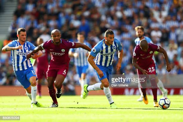 Tomer Hemed of Brighton and Hove Albion chases the ball under pressure from Fernandinho and Vincent Kompany of Manchester City during the Premier...