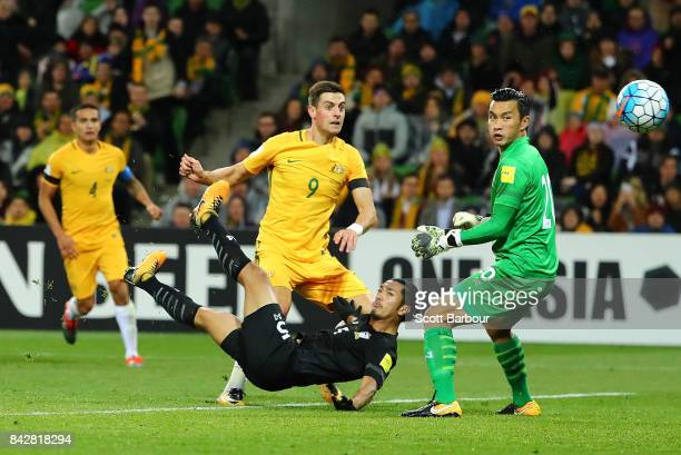 Tomi Juric of the Socceroos has his shot on goal deflected by Adison Promrak of Thailand and past goalkeeper Sinthaweechai Hathairattanakool of...