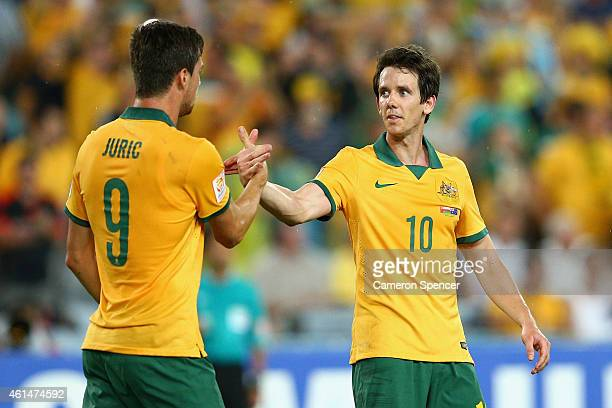 Tomi Juric of the Socceroos is congratulated by team mate Robbie Kruse after scoring a goal during the 2015 Asian Cup match between Oman and...