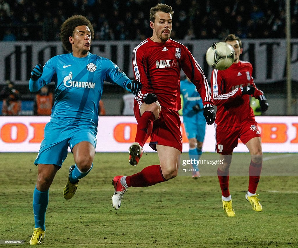 Tomislav Dujmovic of FC Mordovia Saransk (C) vies for the ball with Axel Witsel of FC Zenit St. Petersburg during the Russian Football League Championship match between FC Zenit St. Petersburg and FC Mordovia Saransk at the Petrovsky Stadium on March 17, 2013 in St. Petersburg, Russia.