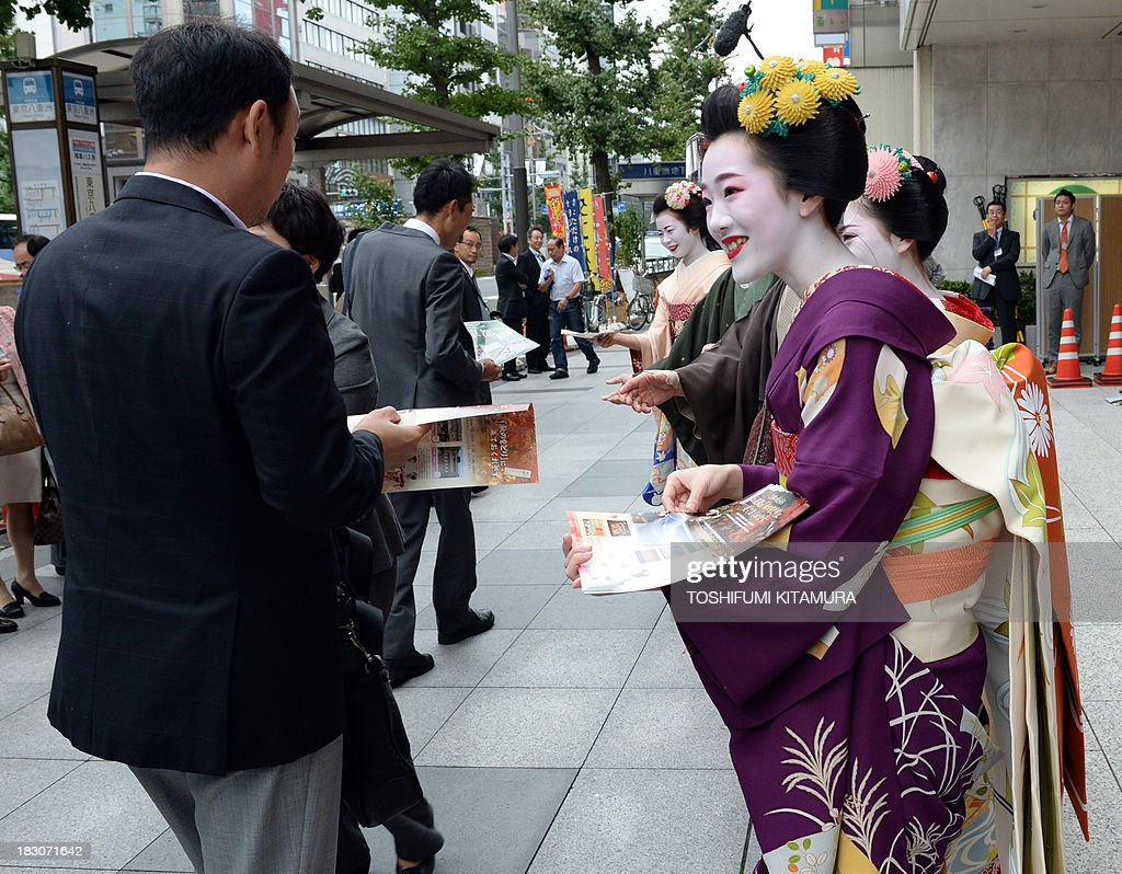 Tomitae, a 'Maiko,' or apprentice geisha, from Gion Higashi (R) hands out Kyoto tourism leaflets to pedestrians during their 'We are alive and well, Kyoto' campaign in Tokyo on October 4, 2013. The campaign was held to attract autumn tourists as Kyoto's scenic tourist area of Arashiyama has recovered from the flood disaster caused by Typhoon Man-yi on September 16, 2013.